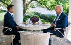 President Moon Jae-in sits opposite of President Joe Biden at an outdoor table.