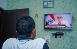 A man watches a television that is playing an announcement from PM Modi.