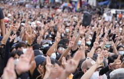 A crowd of people gathered at a protest, lifting their hands with three fingers extended in a gesture of protest against the government.
