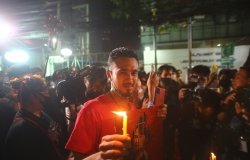A man stands in a crowd of protestors holding a lit candle at night.