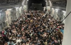 Hundreds of Afghan citizens crowd across the floor of an American military airplane.
