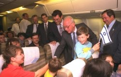Prime Minister Yitzhak Rabin shakes hands with new Russian immigrants on their flight from Russia to Israel, April 27, 1994