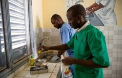 two doctors in healthcare facility cleaning utensils and washing hands