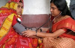 A woman health worker from a charity visited a house in a village to check the blood pressure of a pregnant mother as part of an antenatal checkup, Diamond Harbour, West Bengal.