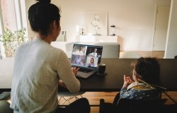 Woman working from home, with her daughter sitting by at the table, having a video conference call