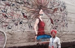 Street Artist Nour Qussini with her artistic piece at the WOW Baladak Street Art Festival in Amman, Jordan: Women on Walls: From Fear to Freedom, 2014.