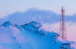 Telecommunication tower on the slope of a snowy mountain. Winter arctic landscape. View of the mountain top and the metal tower with antennas. Communication in the far north in the polar region.