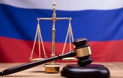 Judge Gavel And Justice Scale On Desk In Front Of Russian Flag
