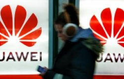 A young woman walks past to advertisement light boxes with Huawei logo in Kiev, Ukraine.