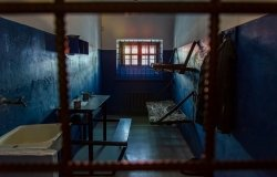 Empty prison cell in Russia. Two beds, a table, a washstand and a toilet are behind bars.