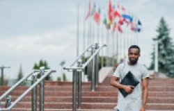 Black student posed with backpack and school items on yard of university, against flags of different countries.