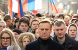 Lyubov Sobol abd Alexei Navalny on march in memory of Boris Nemtsov. People, flag and poster on the background, February 2020.