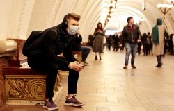 A young man with a backpack sits at a Moscow metro station with a medical mask