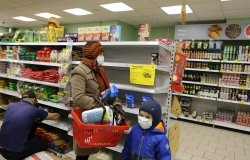 Shoppers in a Moscow grocery store where there are few products on shelves, holding buckwheat and toilet paper.