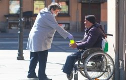 Adult elderly woman in a protective medical mask and gloves gives money to a man in a wheelchair in St. Petersburg.