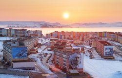 Anadyr, Chukotka, Russia – May 7,2012. Sunrise over the city of Anadyr. Morning view of colorful buildings and sun over the horizon. Cold spring in the Arctic. Anadyr is the easternmost city in Russia.