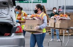 A volunteer loads food into the trunk of a vehicle during a drive-thru food distribution by the Los Angeles Regional Food Bank in Glendora, California