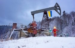 A working engineer at an oil and gas development of an old field checks the operation of mechanisms and control systems in the mountains after a winter in early spring. Flag of Ukraine yellow-blue.