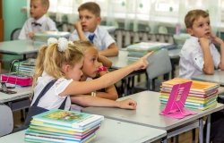 Odessa, Ukraine - September 1, 2015: elementary school students at their desks with textbooks on the first day of the school year. Feast Day of Knowledge. Beginning of a new academic year.