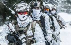 Action in cold conditions. Squad of soldiers with weapons in forest somewhere above the Arctic Circle
